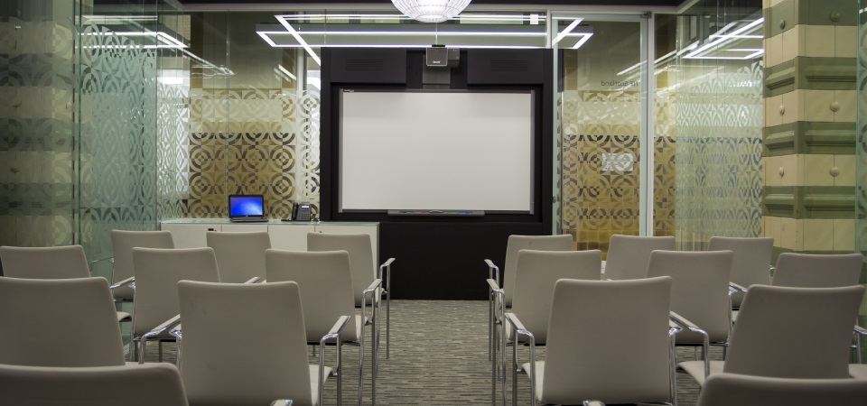 A meeting room with rows of chairs and a screen at the front